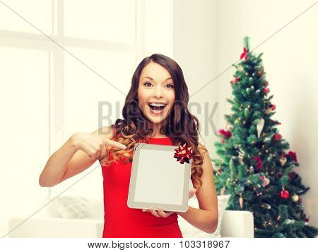 christmas, technology, present and people concept - smiling woman in red dress with blank tablet pc computer screen over living room and christmas tree background