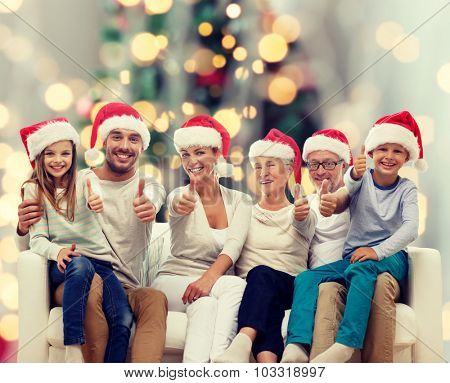 family, happiness, generation, holidays and people concept - happy family in santa helper hats sitting on couch and showing thumbs up gesture over tree lights background