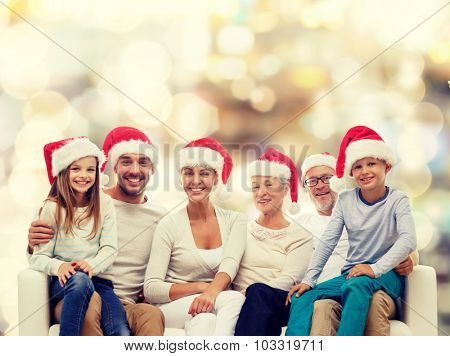 family, happiness, generation, holidays and people concept - happy family in santa helper hats sitting on couch over lights background