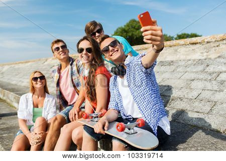 friendship, leisure, summer, technology and people concept - group of smiling friends with skateboard and smartphone taking selfie outdoors