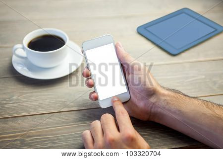 Person showing smartphone at wooden desk