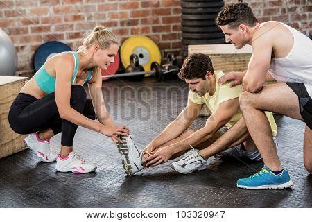 Cropped image of people helping injured man at the gym