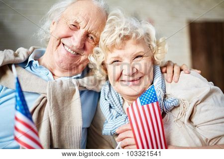 Smiling seniors with flags of USA looking at camera