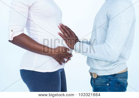 Man touching his pregnant wife belly while standing against white background