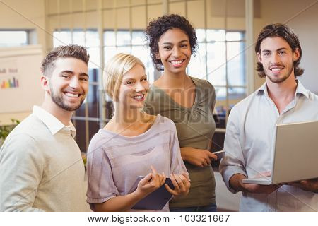 Portrait of smiling business colleagues in creative office