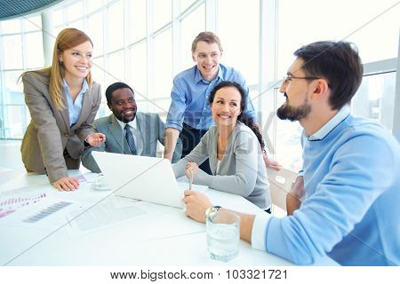 Group of managers looking at their colleague explaining data