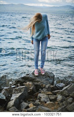 Young woman in jeans and pullover spending weekend by the seaside