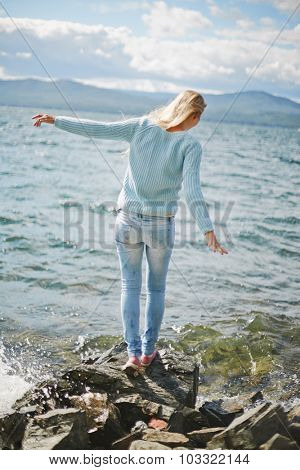 Rear view of blond girl in jeans and pullover standing on stone by the seaside