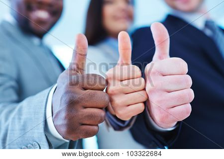 Thumb up gesture shown by group of employees