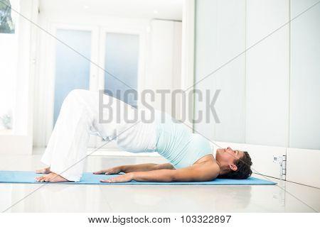 Full length of pregnant woman lying on floor in bridge pose in a fitness studio