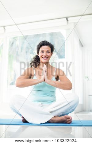 Full length portrait of smiling pregnant woman sitting on exercise mat with joined hands at home