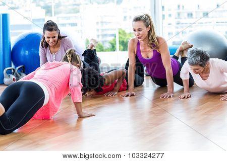 Smiling women exercising on floor in fitness studio