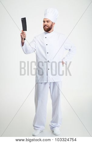 Full length portrait of a happy chef cook holding and looking on knife isolated on a white background
