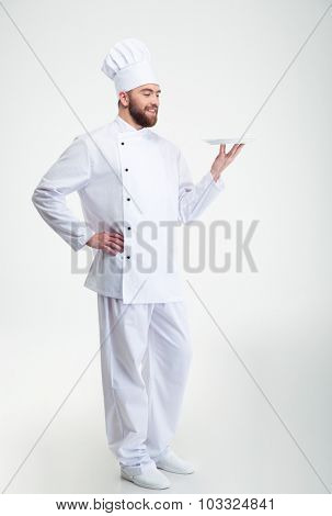 Portrait of a happy male chef cook standing with plate isolated on a white background