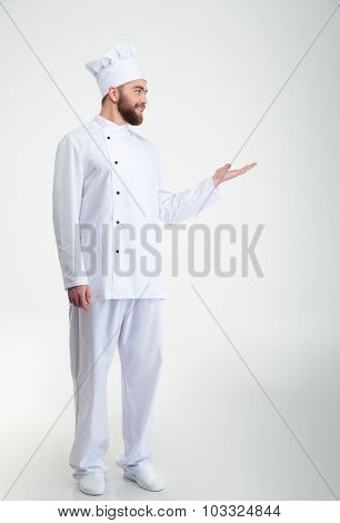 Full length portrait of a smiling chef cook showing copyspace on the palm and looking away isolated on a white background