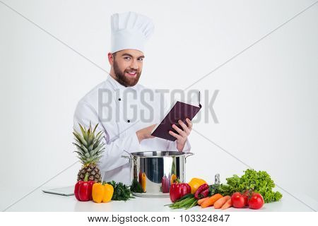 Portrait of a happy male chef cook holding recipe book and preparing food isolated on a white background