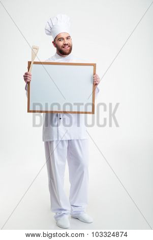 Full length portrait of a smiling male chef cook holding blank board isolated on a white background