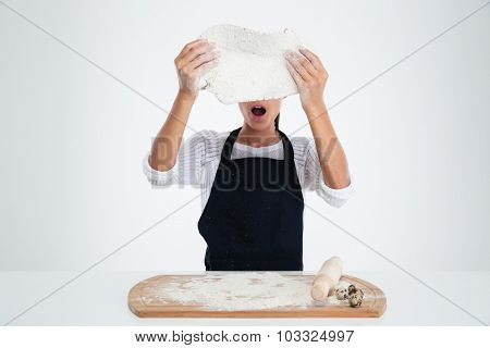 Portrait of a shocked woman preparing dough for pastry isolated on a white background