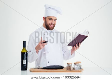 Portrait of a happy male chef cook holding recipe book and glass with red wine isolated on a white background