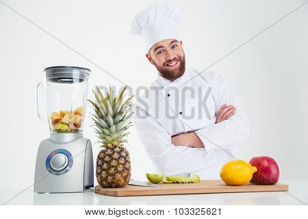 Portrait of a happy chef cook standing with arms folded near table with fruits isolated on a white background