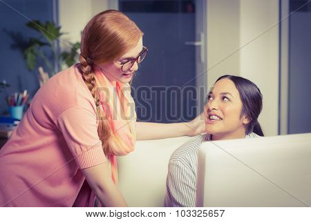 Businesswomen discussing with colleague using computer at desk in office