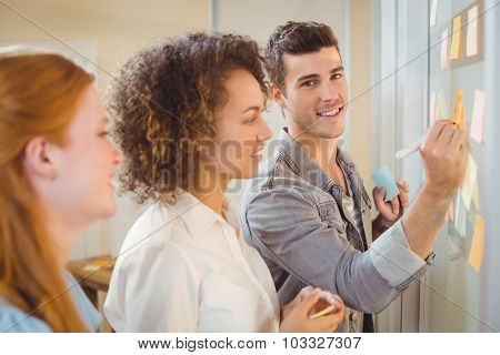 Portrait of businessman writing on glass as female colleagues looking at it during meeting in office