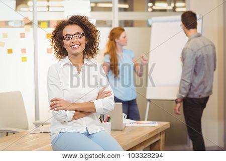 Portrait of businesswoman with arm crossed sitting on table with colleagues looking at whiteboard in background at office
