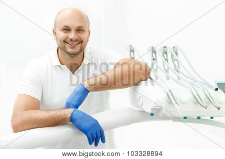 Dentist leaning on the tray of dental instruments