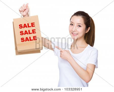 Woman finger point to shopping bag and showing three words of sale