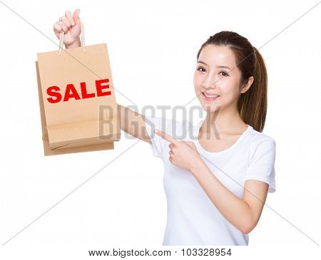 Woman finger point to shopping bag and showing a word of sale