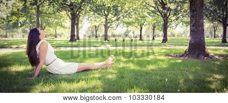 Panoramic view of park while young woman relaxing on grassland