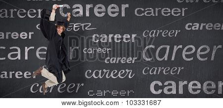 Happy male student in graduate robe jumping against blackboard