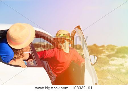 family with kids travel by car in mountains
