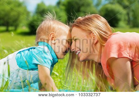 Smiling mother and her child in the green field