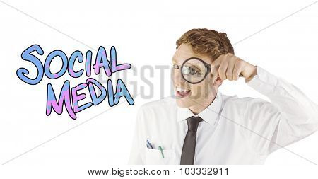 Geeky businessman looking through magnifying glass against social media