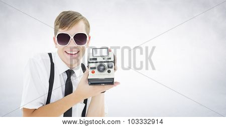 Geeky hipster holding a retro camera against white wall