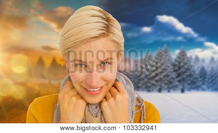 Smiling woman wearing a scarf against autumn changing to winter