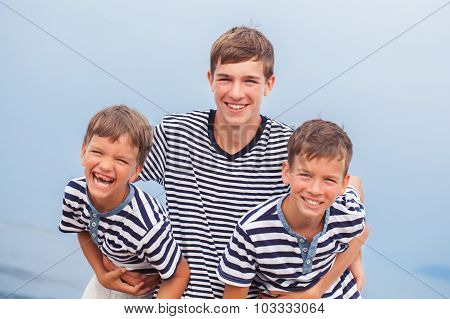 Portrait of three happy funny brothers near sea