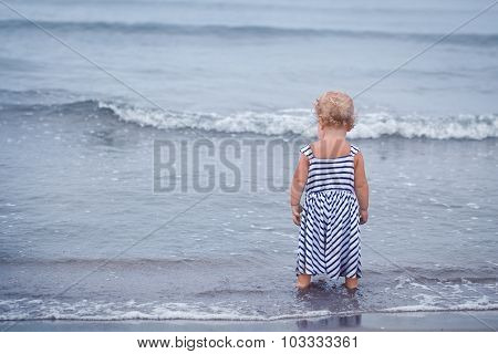 Small Pretty Baby Girl Walking Along Seashore