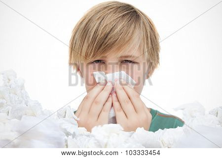 Sick little boy with a handkerchief against used tissues