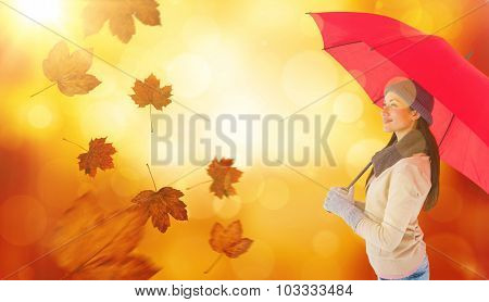 Smiling brunette holding red umbrella against orange abstract light spot design