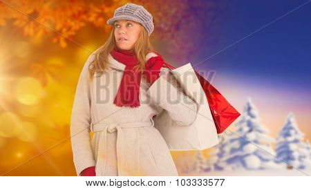 Happy blonde in winter clothes posing against autumn changing to winter