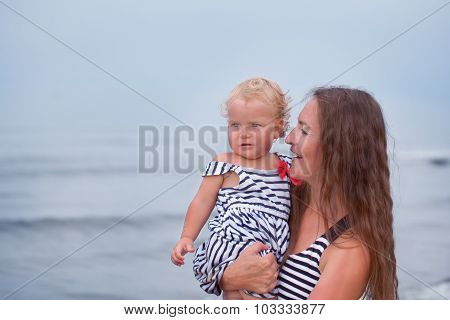 Happy Mother And Small Daughter Go Along The Seashore
