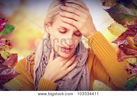 Woman feeling her forehead for a temperature against autumn scene