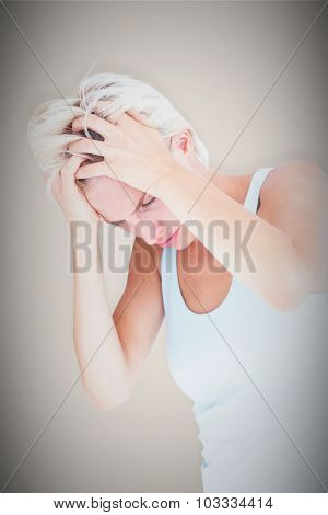 Sad blonde woman with head pain holding her head against grey background with vignette