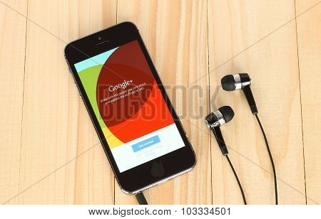 iPhone with Google Plus logotype on its screen and headphones on wooden