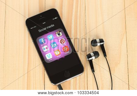 Smart phone with social media logos on its screen and headphones