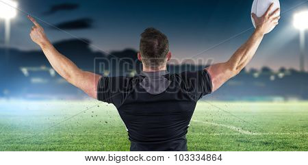 Rugby player celebrating with the ball against pitch