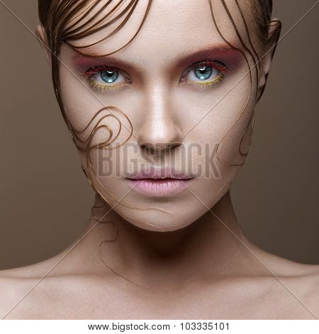 Beautiful girl with bright colored makeup and wet strands of hair on the face. Creative image.