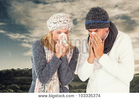 Couple sneezing in tissue against cloudy sky over countryside